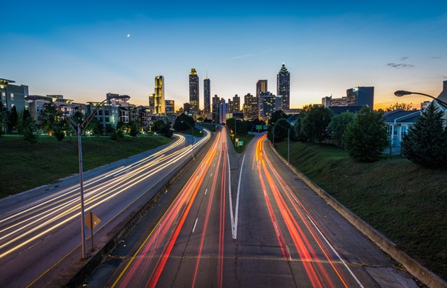 Image of Atlanta skyline by night with speeding tail lights.